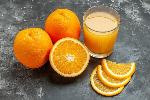 회색 배경에 잘게 잘린 신선한 오렌지와 주스를 자른 비타민 소스의 상위 뷰