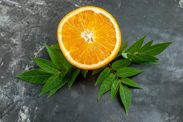 회색 배경에 잎이 있는 신선한 오렌지를 자른 비타민 소스의 상위 뷰