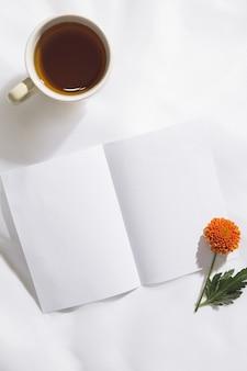 茶マグカップ、オレンジ色の花、テキスト用のスペースと白い紙のボイルファブリックの背景の上から見る