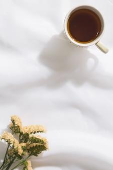 Взгляд сверху предпосылки ткани вуали с кружкой чая и цветков с космосом для текста
