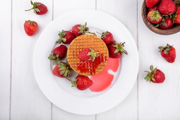 Вид сверху вафельное печенье с клубникой в тарелку и в миску на деревянной поверхности