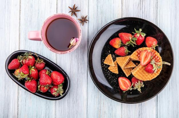 Вид сверху вафельное печенье с клубникой в тарелках и чашка чая на деревянной поверхности