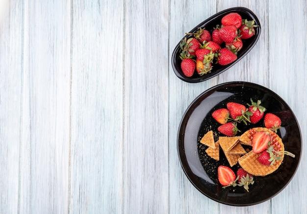 Вид сверху вафельное печенье с клубникой в тарелках на деревянной поверхности