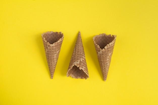 黄色いテーブルの上のワッフルアイスクリームコーンの上面図..クローズアップ。スペースをコピーします。