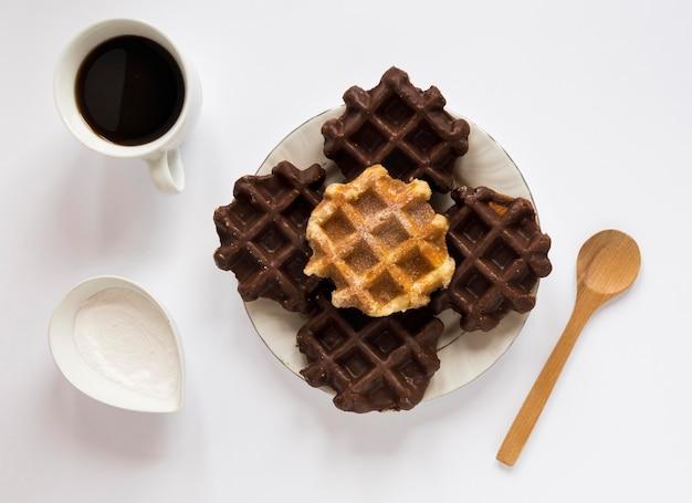 Вид сверху вафли на тарелку с кофе и ложкой