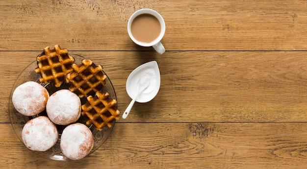 Вид сверху вафли с пончиками и кофе