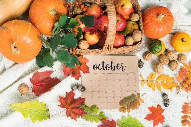 Вид сверху грецких орехов и спелых яблок в корзине с тыквами, желудями и осенними листьями рядом