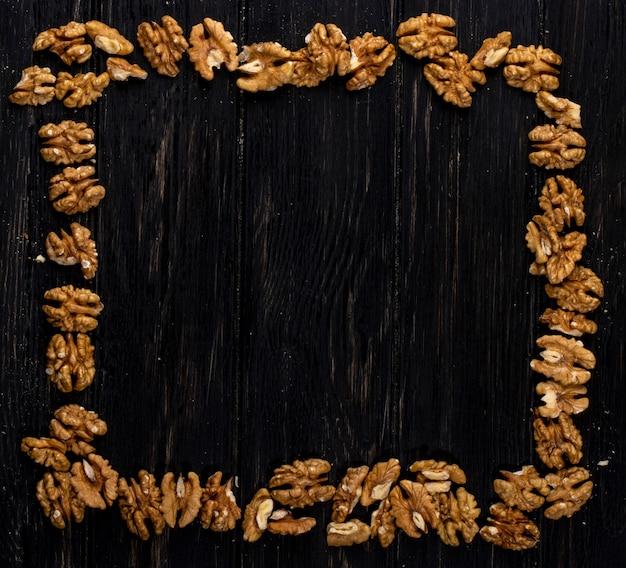 Взгляд сверху грецких орехов аранжированных как рамка на деревенском