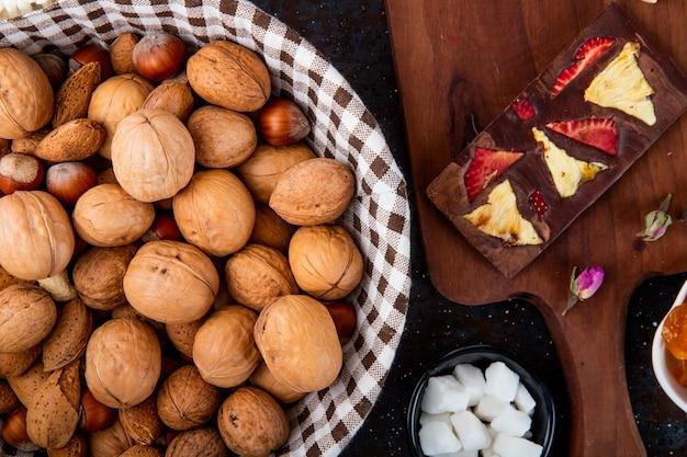 Взгляд сверху грецких орехов в корзине и шоколадных батончиков на деревянной доске на деревенском