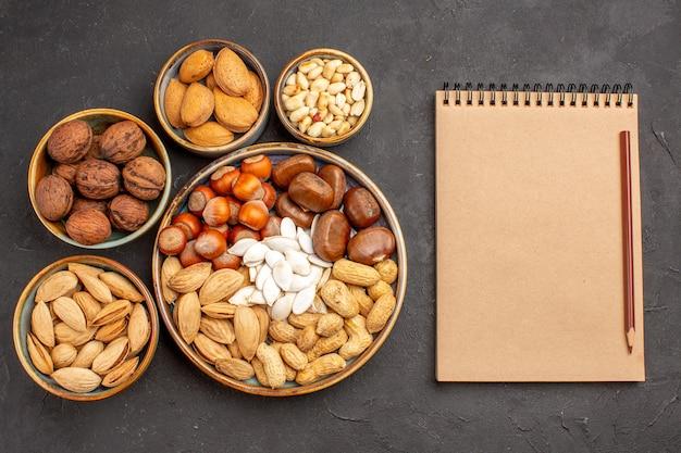 暗い表面のクルミ、ピーナッツ、および他のナッツの上面図