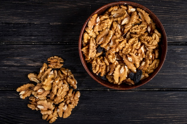 Вид сверху грецких орехов с изюмом в миску на темном деревянном