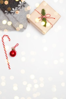 Вид сверху теплых носков со снежинками, подарочной коробке-сюрпризом, завернутой в крафт-бумагу, и бантом на сером фоне. рождественская минимальная композиция с размытыми огнями