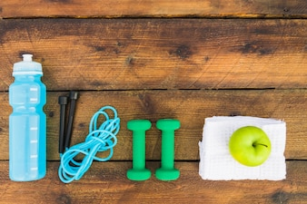 Top view of water bottle; kipping rope; dumbbells; napkin and green apple on wooden background