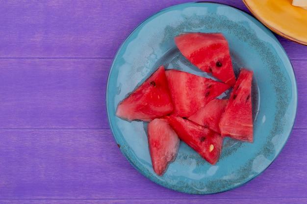 Вид сверху ломтиков арбуза в тарелке на фиолетовом фоне с копией пространства