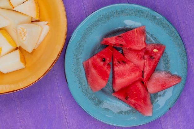 Вид сверху ломтиков арбуза в тарелке с тарелкой ломтиков дыни на фиолетовом фоне