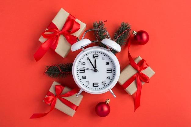 赤い背景に白い目覚まし時計とクリスマスの構成の上面図。閉じる。