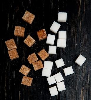 Вид сверху кубов белого и коричневого сахара, разбросанных на темном деревянном фоне