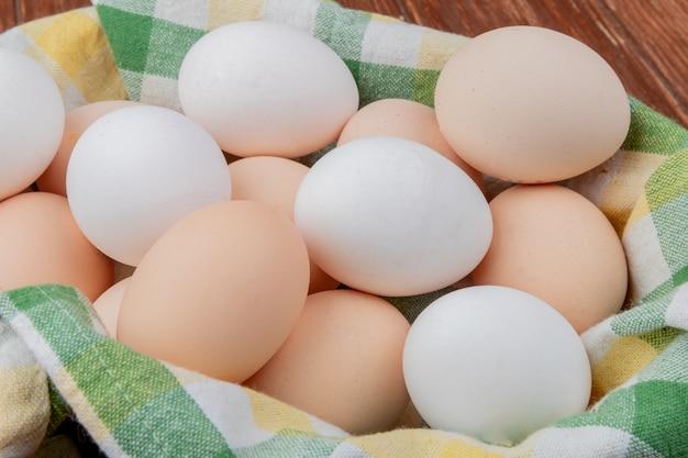 Вид сверху на белые и кремовые куриные яйца на клетчатой скатерти на деревянном фоне
