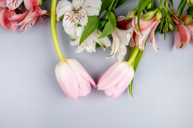 Вид сверху цветы альстромерия белого и розового цвета с розовыми тюльпанами на белом столе