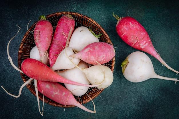 緑の背景の上のバケツの白とピンクがかった赤根菜ビートルートの上面図