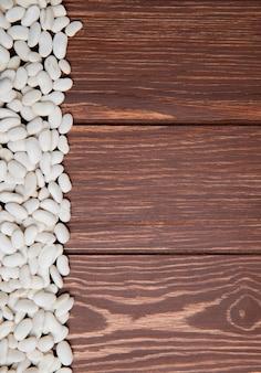 コピースペースを持つ木製の背景に白豆のトップビュー