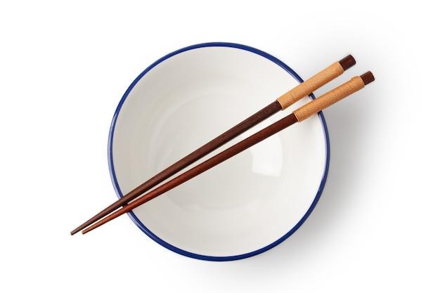 흰색 그릇의 위쪽 보기는 비어 있고 젓가락은 흰색 배경에 격리된 그릇 위에 놓입니다.
