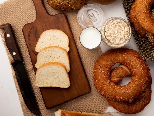 Вид сверху ломтики белого хлеба на разделочную доску с ножом молочные бублики и овсяные хлопья на белом фоне