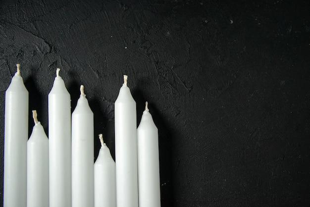 暗い壁に白いろうそくのトップ ビュー