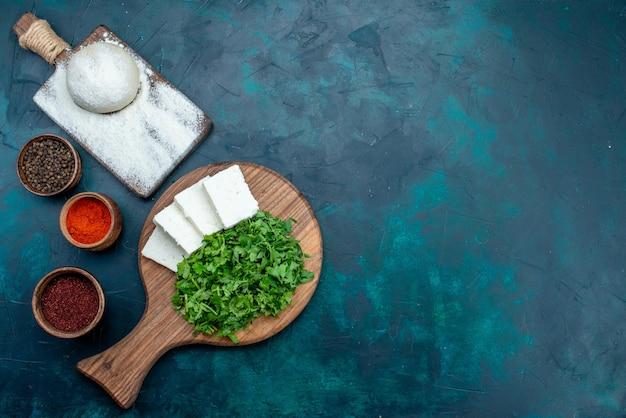 暗い表面に新鮮な緑と調味料と白いチーズの上面図