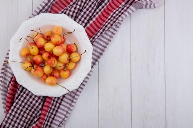 Вид сверху белой вишни в тарелке на клетчатом полотенце на белой поверхности