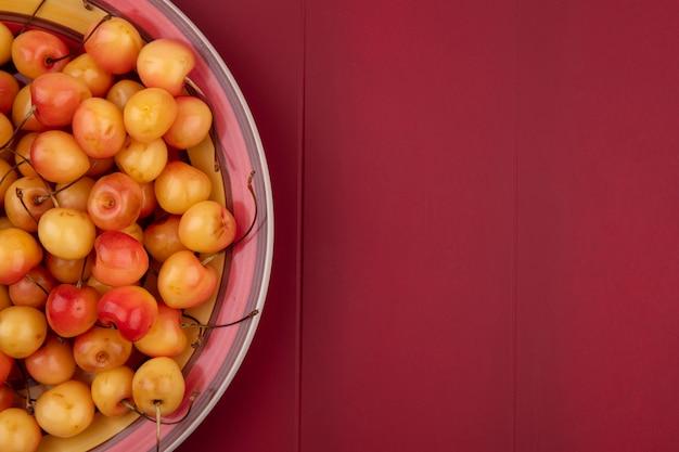Вид сверху белой вишни на тарелке на красной поверхности