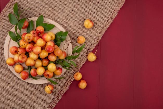 Вид сверху белой вишни на подставке на бежевой салфетке на красной поверхности