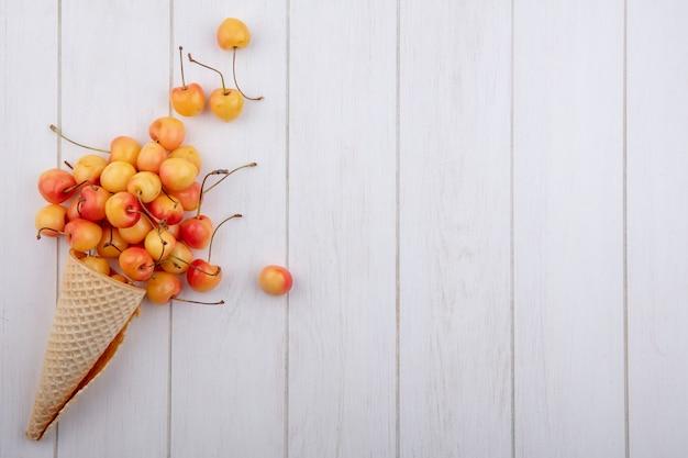 Вид сверху белой вишни с вафельным рожком на белой поверхности
