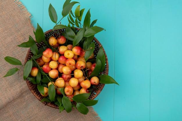 Вид сверху белой вишни с ветвями листьев в корзине на бежевой салфетке на бирюзовой поверхности