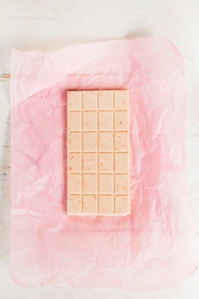 Top view of white chocolate bar on pink paper wrapper