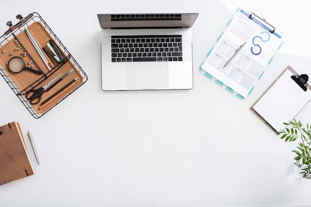 Вид сверху белого copyspace, окруженного ноутбуком, корзиной с канцелярскими принадлежностями, чистыми бумагами и буфером обмена с финансовыми документами