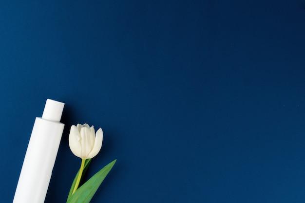 꽃과 흰색 화장품 용기의 상위 뷰