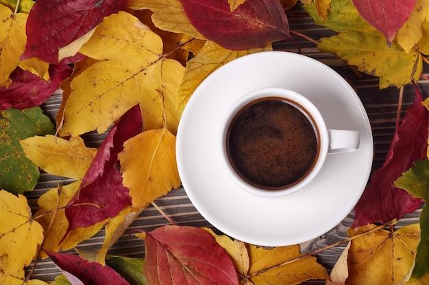 白い一杯のコーヒーと木のテーブルの周りの秋の黄色の葉の上面図