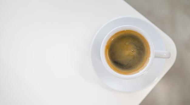 白いテーブルにホットブラックコーヒーとクレマの白いカップのトップビュー