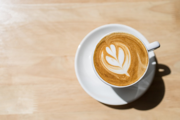 Взгляд сверху белой чашки горячего latte кофе с искусством формы сердца пены молока на деревянном столе под солнечным светом и тенью утра.