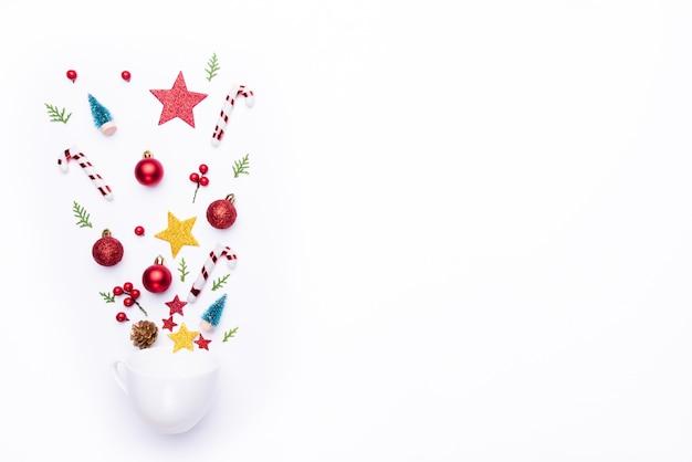 Вид сверху белые чашки всплеск рождественские украшения с подарочной коробке на белом фоне.