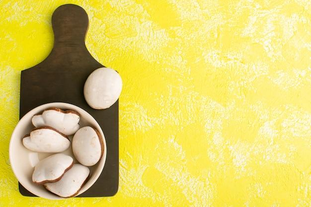 Вид сверху белого вкусного печенья, изолированного на желтой поверхности