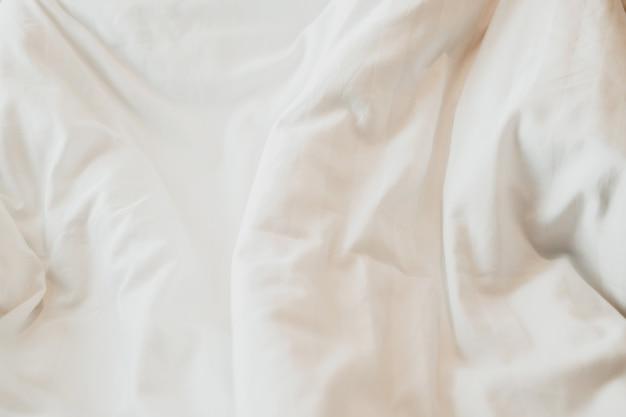 Вид сверху белого пухового одеяла на кровати с солнечным светом. спальня с белой кроватью.