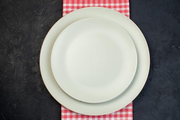 여유 공간이 있는 검정색 배경에 빨간색 벗겨진 수건에 흰색 빈 접시의 상위 뷰