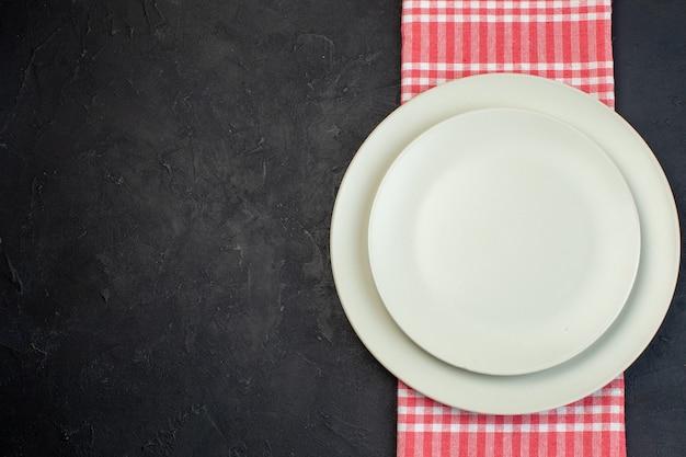 여유 공간이 있는 검정색 배경의 왼쪽에 있는 빨간색 벗겨진 수건에 흰색 빈 접시의 위쪽 보기