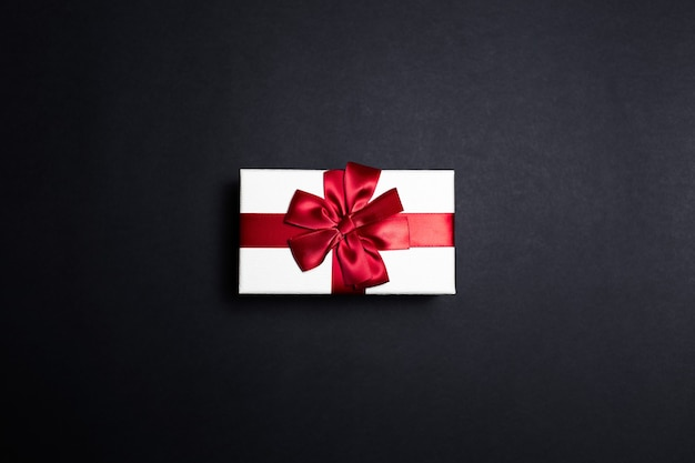 검은 색 표면에 붉은 활과 흰색 선물 상자의 상위 뷰