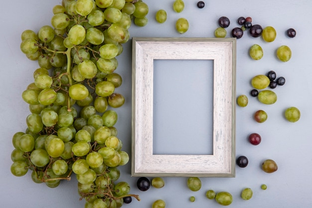 コピースペースと灰色の背景に白ブドウとブドウの果実を持つフレームのトップビュー