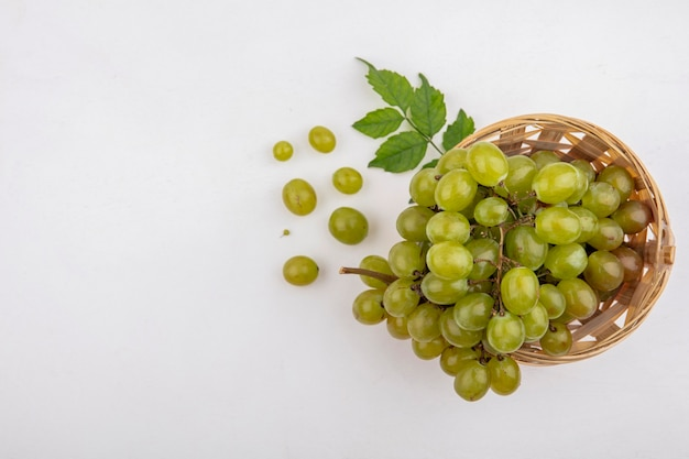 Вид сверху белого винограда в корзине и на белом фоне с копией пространства