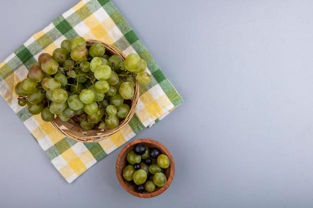 Вид сверху белого винограда в корзине на клетчатой ткани и виноградных ягод в миске на сером фоне с копией пространства