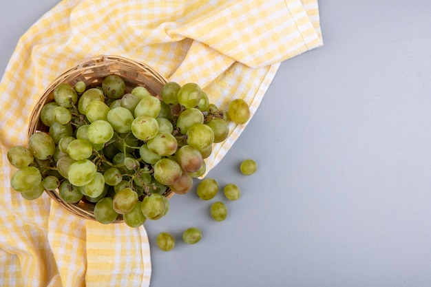 Вид сверху белого винограда в корзине на клетчатой ткани и на сером фоне с копией пространства